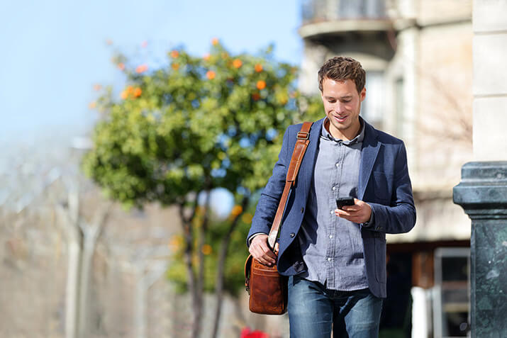 Young urban businessman professional on smartphone walking in st